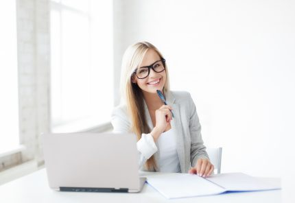 indoor picture of smiling woman with documents and pen